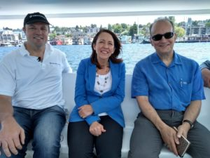 Andy Rebele, CEO of Pure Watercraft, US Senator Maria Cantwell, and Tom Ranken, CEO of the CleanTech Alliance on the water in a boat powered by and Pure Watercraft electric motor.